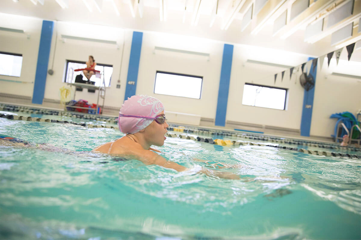 A young girl is exercising in the YMCA swimming pool with goggles and a swim cap.