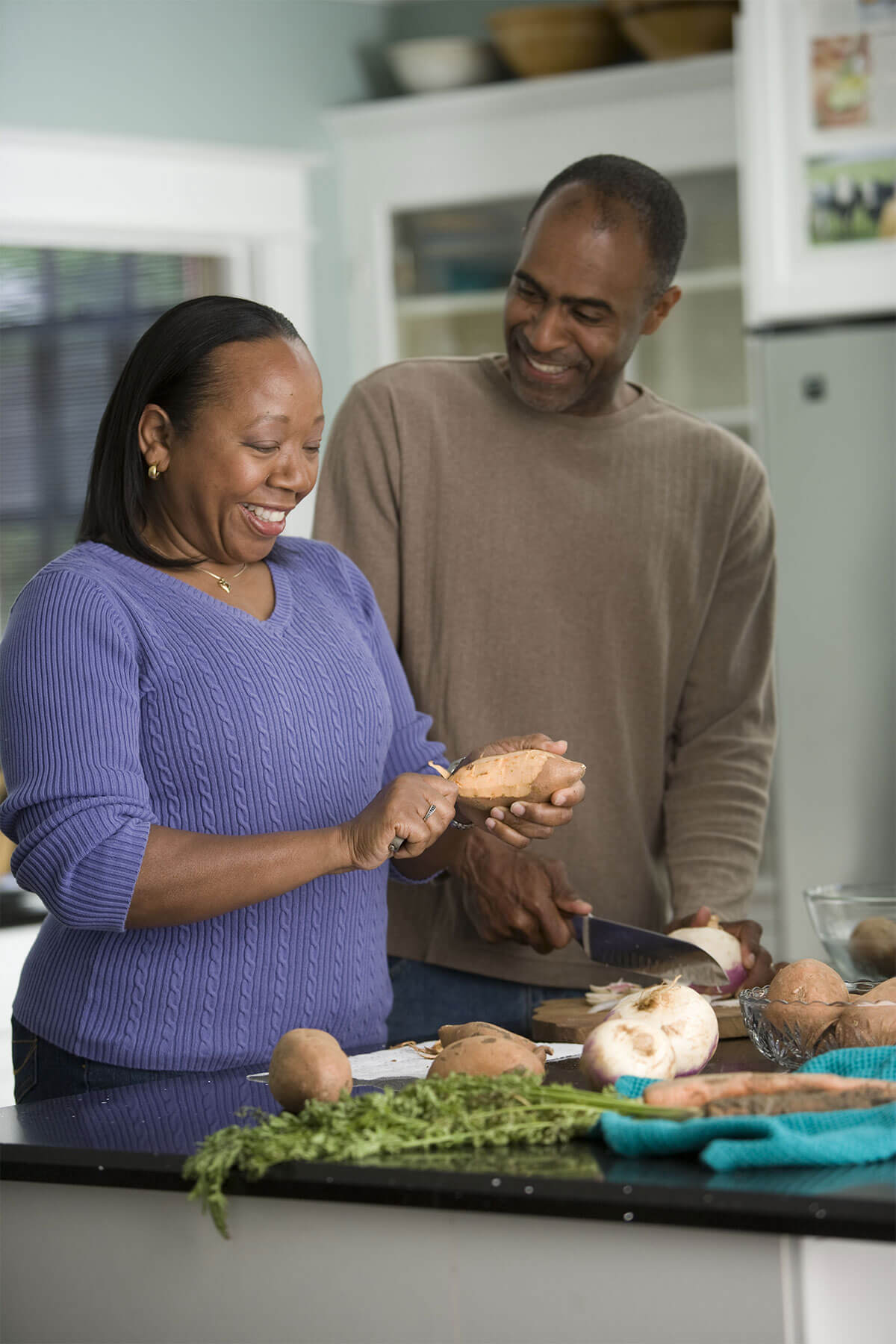 An African American couple cooks a healthy meal for dinner.
