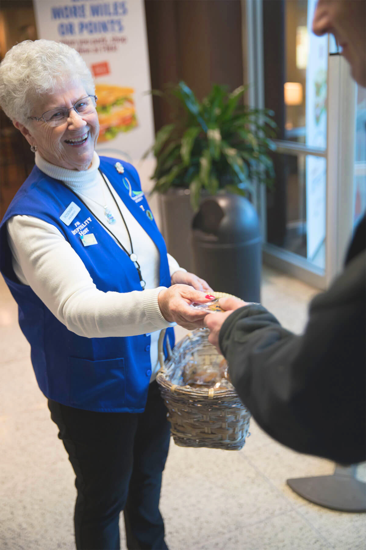 A woman is handing a cookie to the passengers who just landed at the Fort Wayne airport
