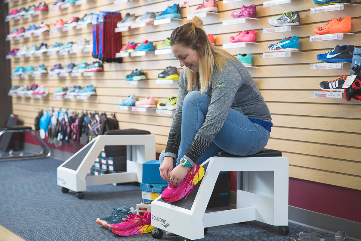 A young girl is trying on shoes at the 3Rivers Running Company.