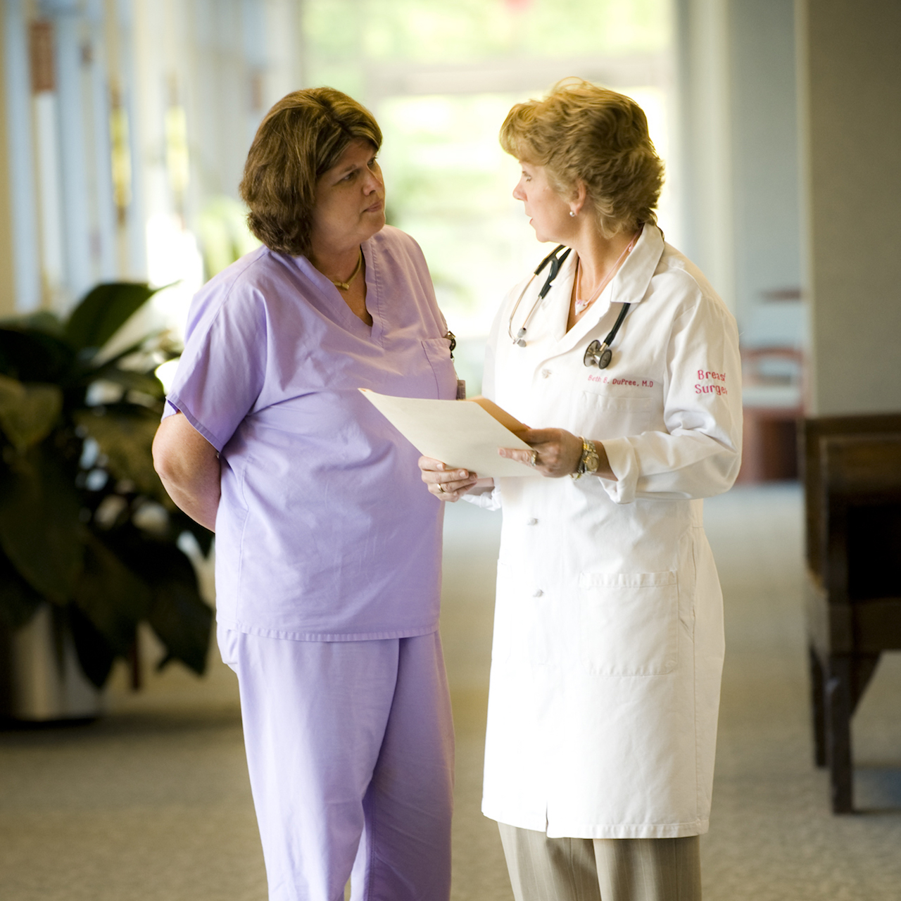 A physician and nurse are speaking to one another in a PHP participating provider facility.